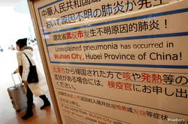 FILE PHOTO: A woman wearing a mask walks past a quarantine notice about the outbreak of coronavirus in Wuhan, China at an…