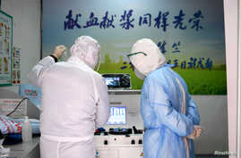 Medical workers in protective suits inspect equipment at a blood donation room of the Renmin Hospital of Wuhan University in…