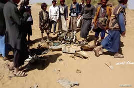 People inspect purported plane crash site in, said to be, Al-Jawf, Yemen on, said to be, February 15, 2020 in this still image…