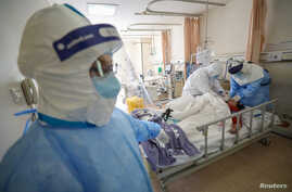Medical workers in protective suits attend to a patient inside an isolated ward of Wuhan Red Cross Hospital in Wuhan, the…