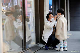 A man and a boy wear masks to prevent contracting a new coronavirus at Myeongdong shopping district in Seoul, South Korea,…
