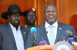 South Sudan's ex-vice President and former rebel leader Riek Machar flanked by President Salva Kiir Mayardit address a news…