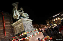 Candles are placed around the Brothers Grimm monument during a vigil for the victims of a shooting in Hanau, near Frankfurt,…