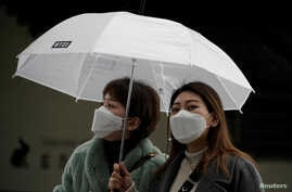 Passengers wearing masks to prevent contacting the coronavirus walk outside Seoul Railway Station in Seoul, South Korea,…