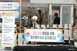 South Korean soldiers wearing masks to prevent contacting the coronavirus stand guard at a checkpoint of a military base in…