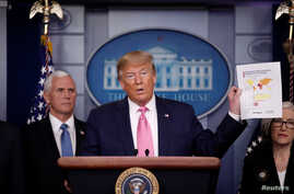 U.S. President Donald Trump holds a document as he gives a news conference at the White House in Washington, U.S., February 26,…