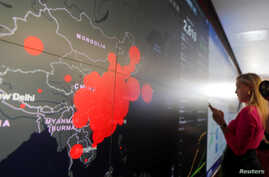 """A reporter stands in front of a coronavirus global map during a tour of the """"secretary's operation center"""" as part of a…"""
