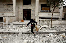 A Syrian boy removes a dead chicken from the debris of a building hit by an air strike in Idlib, Syria February 28, 2020…