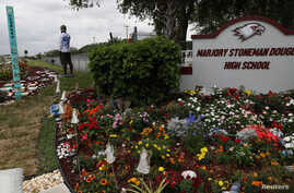 Chad Williams, 19, a survivor of the Marjory Stoneman Douglas high school shooting, stands alone at a memorial garden outside…