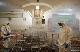 Members of the medical team spray disinfectant to sanitize indoor place of Imam Reza's holy shrine, following the coronavirus…