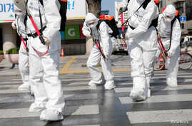 South Korean soldiers wearing protective gear sanitize a street in front of the city hall after the rapid rise in confirmed…