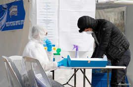 A paramedic in a protective suit helps a man as he prepares to vote in a special polling station set up by Israel's election…