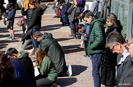 The faithful kneel and pray during Mass in the open air, after Italy's bishops ordered Masses not be held in churches in order…