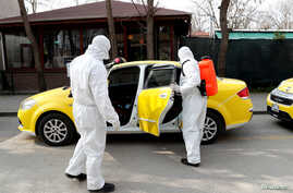Municipality workers wearing protective suits sanitise a taxi in Karaagac district against the coronavirus disease (COVID-19)…