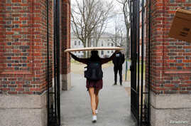A student carries a box to her dorm at Harvard University, after the school asked its students not to return to campus after…