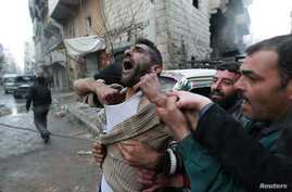 FILE PHOTO: A father reacts after the death of two of his children, whom activists said were killed by shelling by forces loyal…
