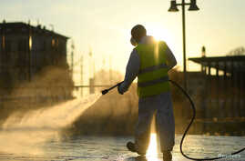 A worker sanitizes a street on the fourth day of an unprecedented lockdown across of all Italy imposed to slow the outbreak of…