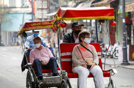 Foreign tourists wear protective masks while traveling on three-wheel cycle along old quarters streets in Hanoi, Vietnam March…