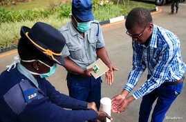 Police officer shows a visitor how to disinfect his hands against the spread of coronavirus disease (COVID-19) at State House…