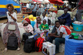 Passengers wait to board a disinfected public transport bus as they leave for the villages amid concerns about the spread of…