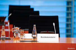 The empty chair of German Chancellor Angela Merkel is seen as she participates in the weekly cabinet meeting by video, since…