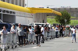 Shoppers queue to stock up on groceries at a Makro Store at Strubens Valley, ahead of a nationwide lockdown for 21 to try to…