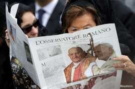 FILE PHOTO: A woman reads a copy of the Vatican newspaper L'Osservatore Romano as she waits for the canonisation ceremony in St…