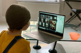 A school kid socializes with peers online following school closures due the spread of the coronavirus disease (COVID-19)…