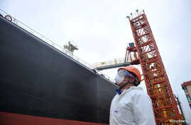 A dock worker wearing a face mask to prevent the spread of the coronavirus disease (COVID-19) looks at an oil tanker unloading…