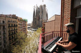 Amateur pianist Alberto Gestoso Arce, 37, plays the piano from his balcony for neighbours, near the Sagrada Familia basilica,…