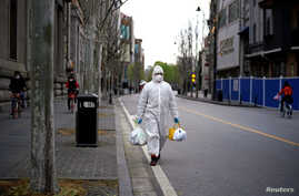 A man wearing a hazmat suit walks on a street in Wuhan, Hubei province, the epicenter of China's coronavirus disease (COVID-19)…