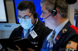 FILE PHOTO: Traders work on the floor of the New York Stock Exchange (NYSE) in New York, U.S., March 20, 2020. REUTERS/Lucas…