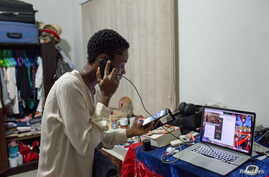Illustrator Sena Ahadji speaks to a client on the phone from her house in Accra, Ghana, July 24, 2015. Young artists in Ghana's…