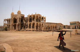 A man carries a table as he walks past the ruins of a building in the port city of Massawa, Eritrea July 22, 2018. Picture…
