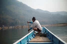 A local villager drive a boat where the future site of the Luang Prabang dam will be on the Mekong River, outskirt of Luang…