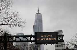 One World Trade is seen behind a sign that flashes an emergency alert, as the coronavirus disease (COVID-19) outbreak continues…