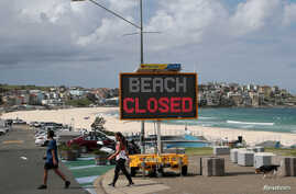"People walk past a ""Beach Closed"" sign at Bondi Beach, as the beach remains closed to prevent the spread of the coronavirus…"