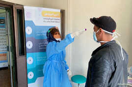 A nurse checks the temperature of a man before he enters a medical clinic, following the outbreak of the coronavirus disease …