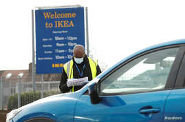 People queue in their cars at an NHS drive through coronavirus disease (COVID-19) testing facility in the car park of Ikea in…