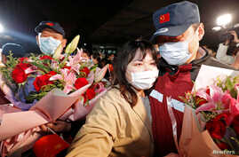 A medical team member hugs a family member at the end of a 14-day quarantine following the team's return from Wuhan, the…