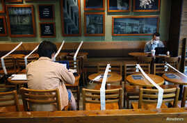 Tables and chairs are taped up to keep social distancing at a Starbucks coffee shop, following the novel coronavirus disease …