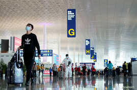 Travellers are seen at the Wuhan Tianhe International Airport after travel restrictions to leave Wuhan, the capital of Hubei…