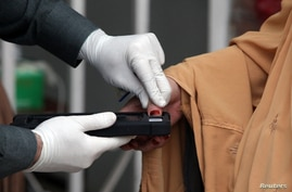 A woman gets her thumb verification to receive cash from a counter of Ehsaas Emergency Cash program, introduced by the…