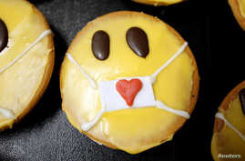 Cakes that look like emojis with protective masks are seen at the bakery Schuerener Backparadies, as the spread of the…