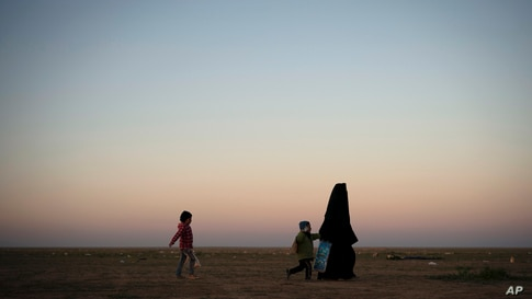 A woman walks with her children at a U.S.-backed Syrian Democratic Forces (SDF) screening area after being evacuated out of the last territory held by Islamic State militants, in the desert outside Baghuz, Syria, March 1, 2019.