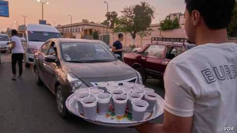 Young Egyptian men distribute juice and dates to passersby and drivers in their cars at the time of Iftar.