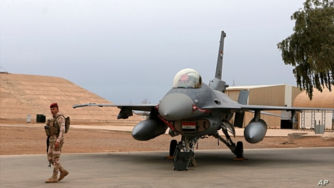 FILE - An Iraqi army soldier stands guard near a U.S.-made Iraqi Air Force F-16 fighter jet at the Balad Air Base, Iraq, Feb. 13, 2018. Arab media reported a drone strike Tuesday on the area near the base.