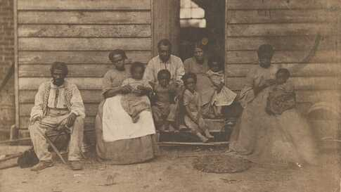 African American slave family or families posed in front of wooden house on a plantation in 1862.