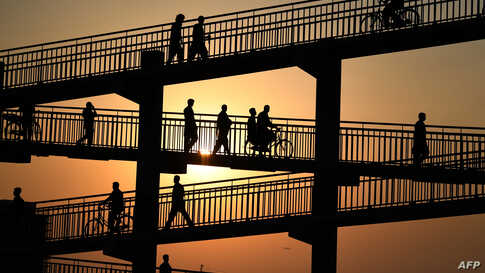 Laborers cross a pedestrian bridge in Dubai, United Arab Emirates.