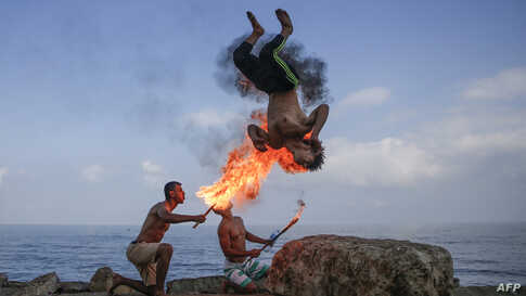 Palestinian men perform fire breathing on the beach during the summer in Gaza City.